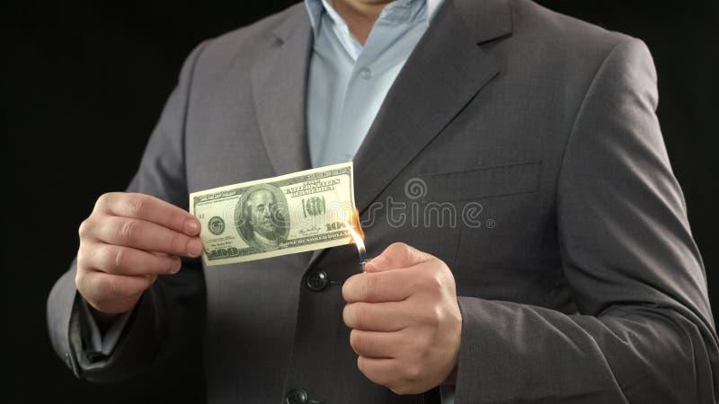 Hundert Dollarschein auf Feuer, männlicher Bankrott, verlierendes Geld, Inflation lizenzfreie stockfotografie