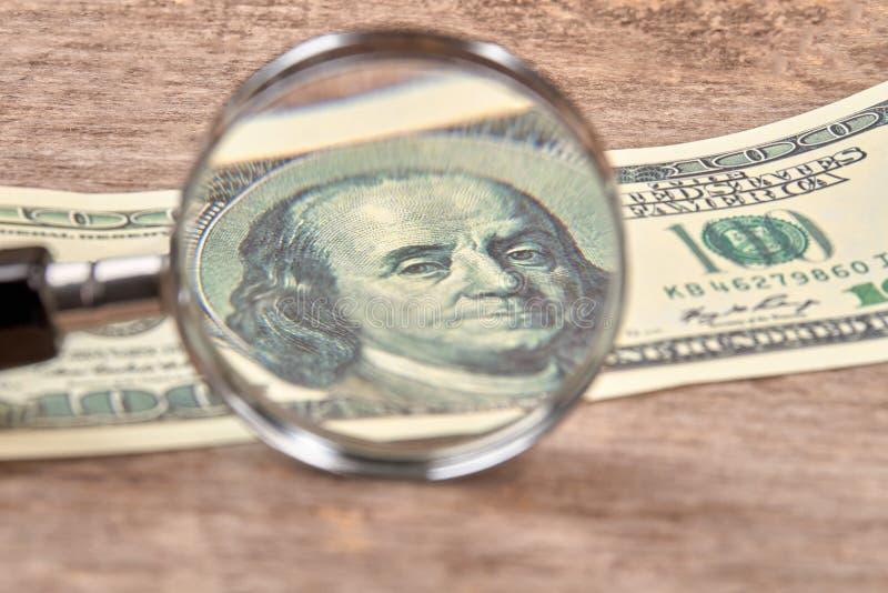 Hundert Dollarschein unter einem Vergrößerungsglas stockfoto
