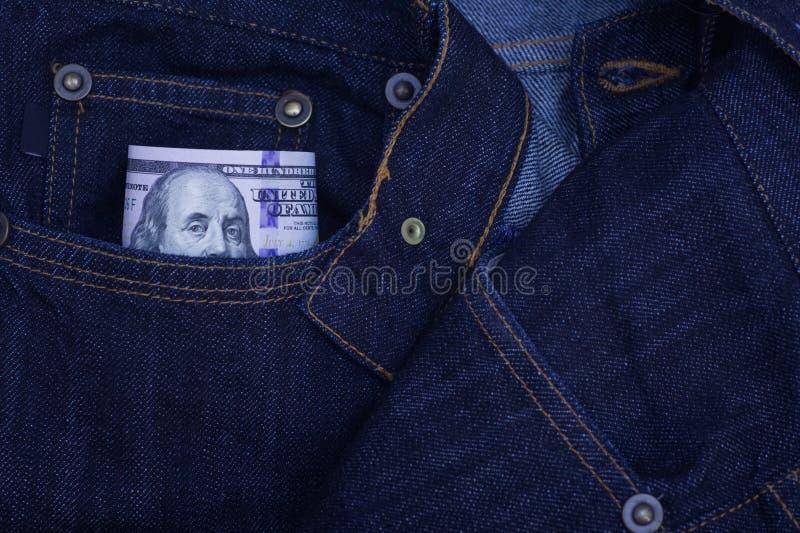 Hundert Dollarscheine, die aus der Tasche von Denimjeans heraus haften lizenzfreie stockbilder