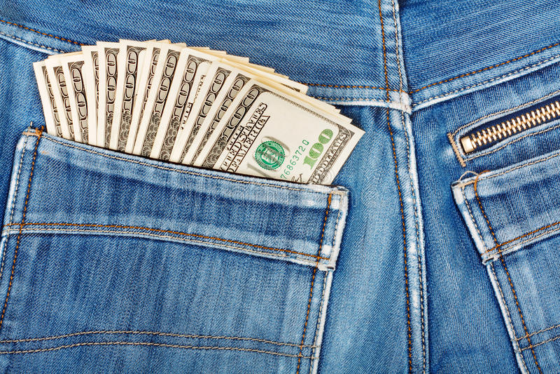 Hundert Dollarscheine, die in der Gesäßtasche des Denims haften stockfoto
