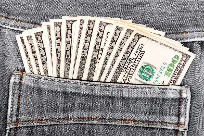 Hundert Dollarscheine, die in der Gesäßtasche von Denimjeans haften lizenzfreie stockfotos