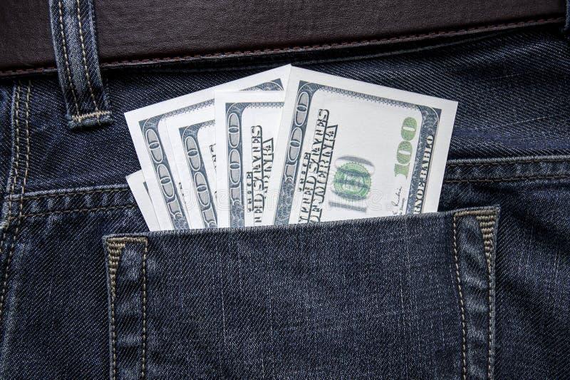 Hundert Dollarscheine haften aus der Gesäßtasche von Jeans heraus lizenzfreie stockbilder