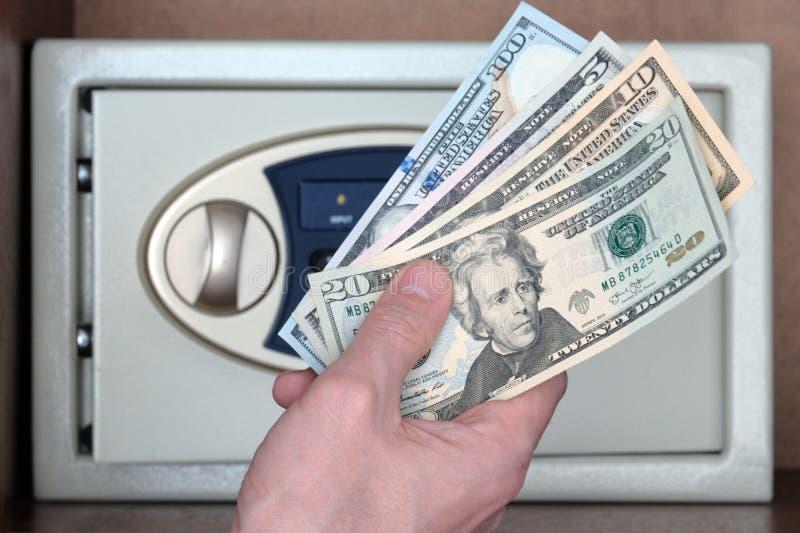 Hundert, zwanzig, zehn und fünf Dollar in der Hand eines Mannes vor dem hintergrund eines Safes Das Konzept von Geld herein speic lizenzfreies stockbild
