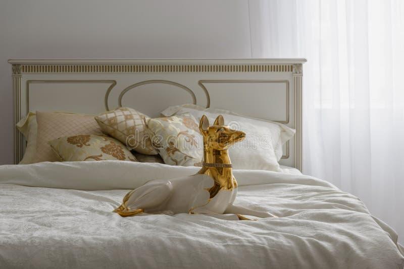 Hundestatuette auf Bett mit weißem Leinen stockfoto