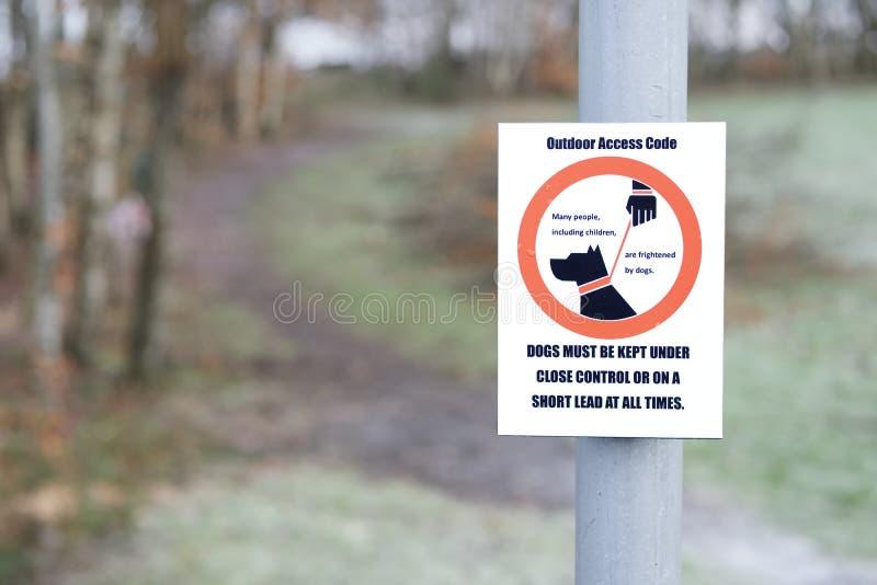 Hundewegweiser muss auf Park-Zugangkennziffer der kurzen Führung gehalten werden im Freien stockbilder