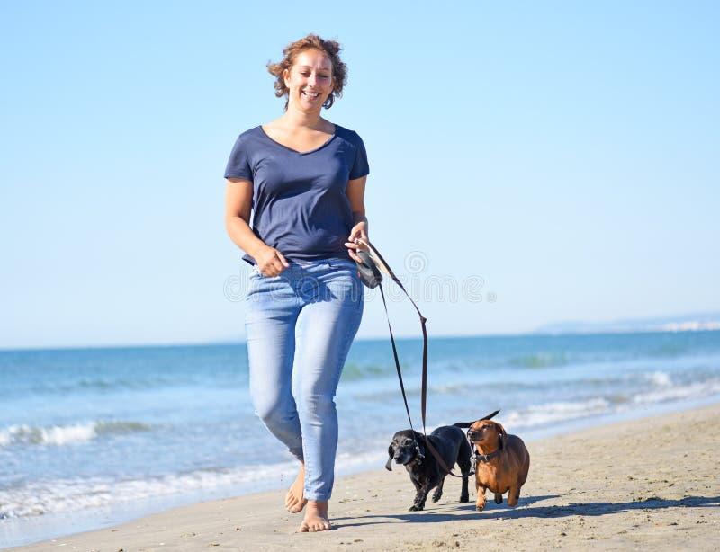 Hundkapplöpning och kvinna på stranden royaltyfri bild