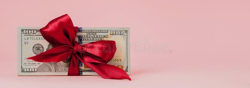 Hundra dollar gåva wraped med ett rött band på rosa bakgrund arkivfoto