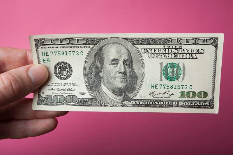 Hundra dollar närbild i hand på en rosa bakgrund royaltyfria foton