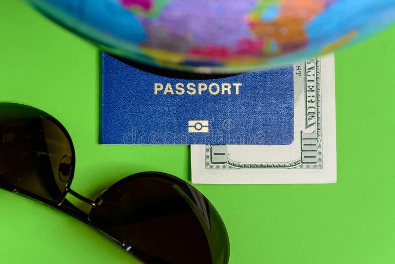 Hundra dollar och ett pass på en grön bakgrund med en översikt av jordklotet arkivfoton