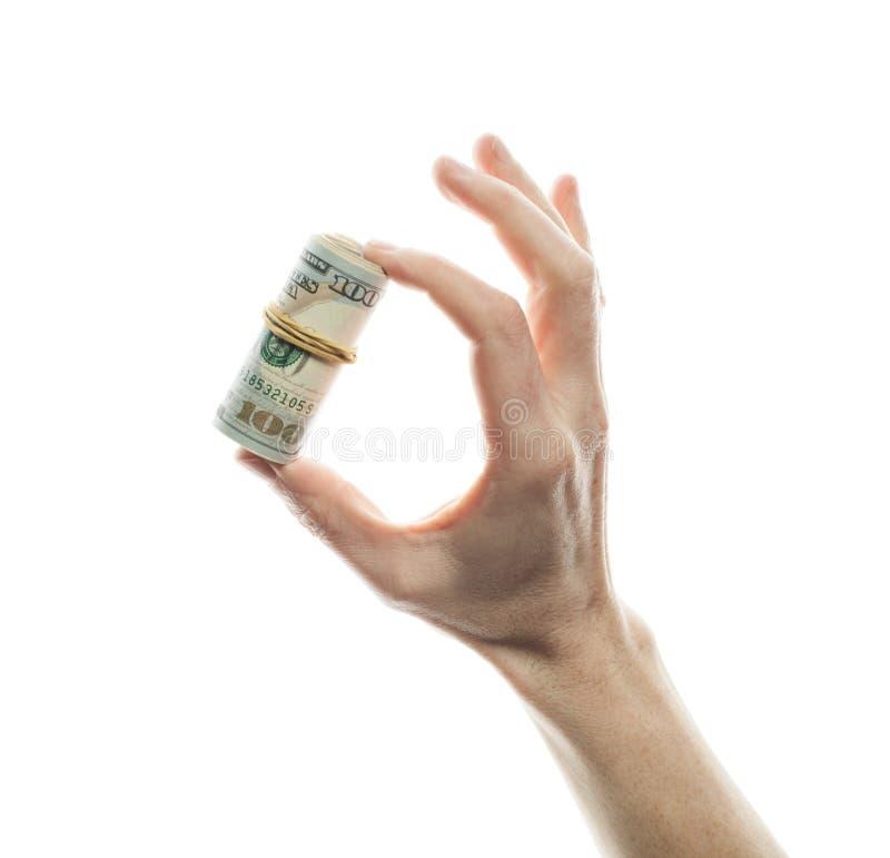 Hundra dollarräkningar i en rulle i den manliga handen som isoleras över vit bakgrund royaltyfri foto