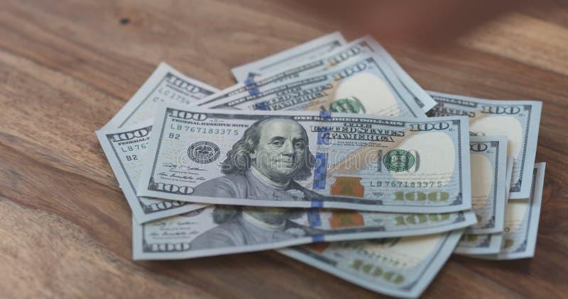 Hundra dollarräkningar på den wood tabellen royaltyfri foto