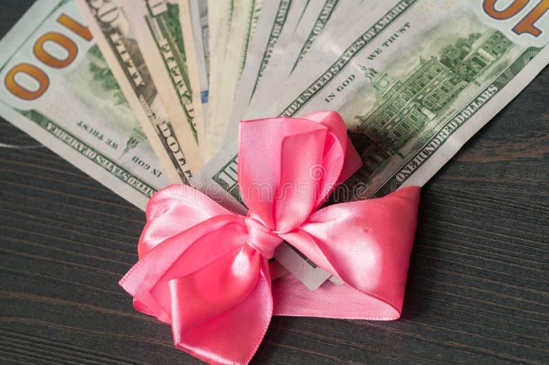 Hundra dollarräkningar som slås in i ett rosa band royaltyfria bilder