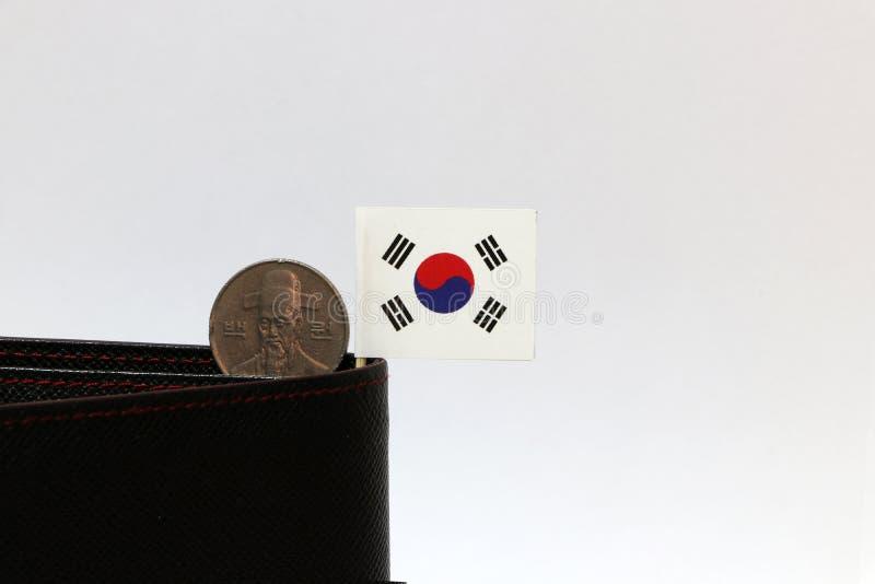 Hundra koreanska segrade mynt på avers, KRW och den mini- Sydkorea flaggapinnen på den svarta plånboken med vit bakgrund royaltyfria bilder