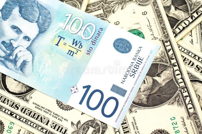 Hundra serbiska dinar med amerikanen en dollar räkningar arkivbild