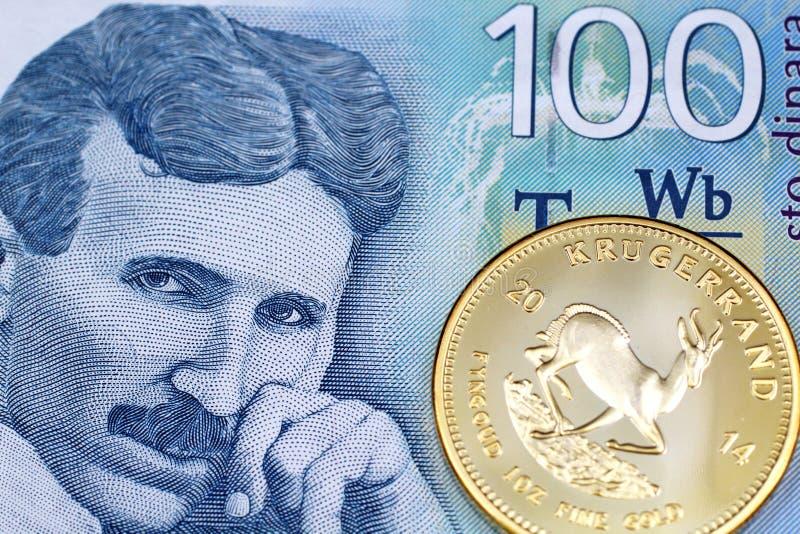 Hundra serbiska dinarsedel med ett guld- krugerrandmynt arkivfoton