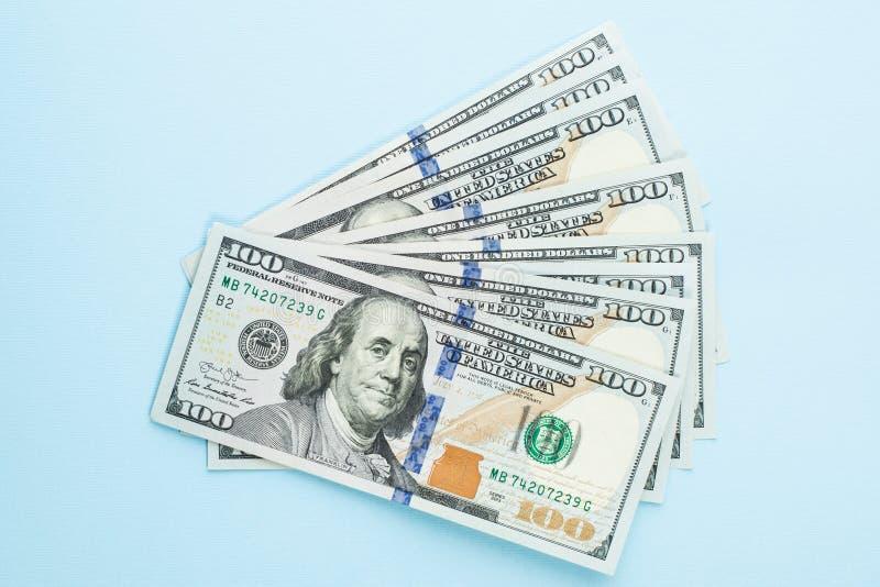 Hundra US dollarpengarkassa på blå bakgrund Amerikanska dollar 100 anmärkningsvinstbegrepp arkivfoto