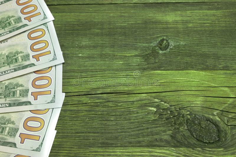 Hundra USA dollarräkningar på ruffar mot den gröna Wood tabellöverkanten royaltyfri foto