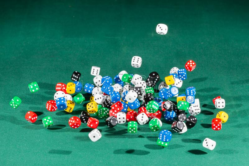 Hundred colored dices falling on a green table. Hundred dices with different colors falling on a isolated green table royalty free stock image