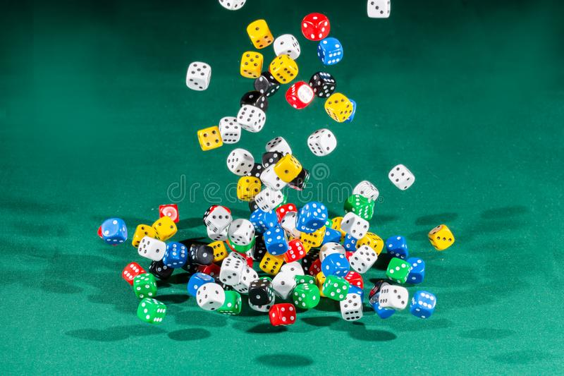 Hundred colored dices falling on a green table. Hundred dices with different colors falling on a green table royalty free stock photography