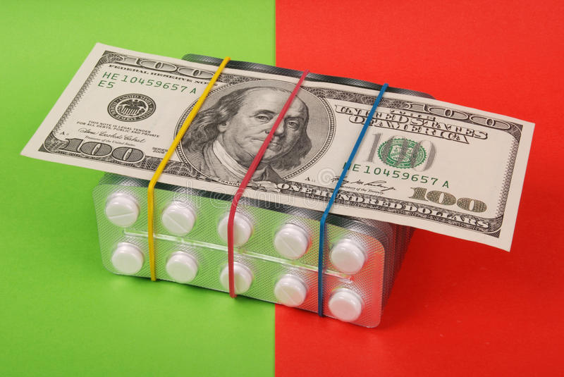 Hundred dollars. Lays on packing of white tablets. Red and green background stock photos