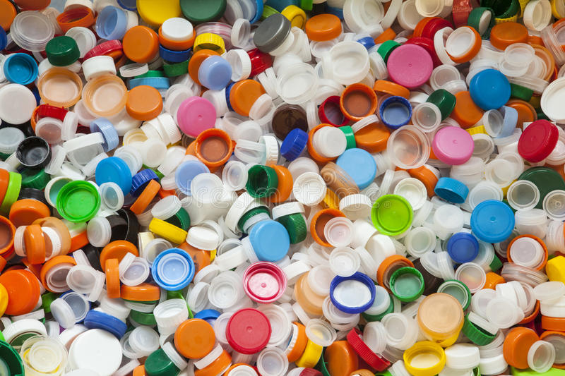 Hundreds of Brightly Colored Plastic Bottle Caps. Hundreds and hundreds of vividly colored plastic screw-on bottle caps, ready to use for inspiring recycled or royalty free stock image