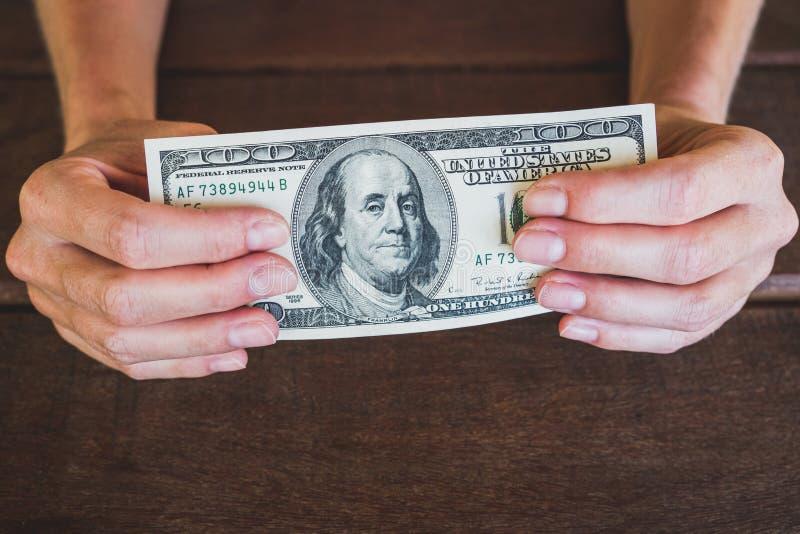 Hundres-Dollar - zwei Hände, die 100 Dollarscheinbargeld halten lizenzfreie stockfotografie