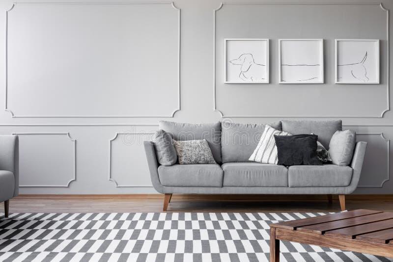 Hunds affischer på den gråa väggen av ljus vardagsrum med den bekväma gråa soffan med kuddar, verkligt foto med kopieringsutrymme royaltyfri foto