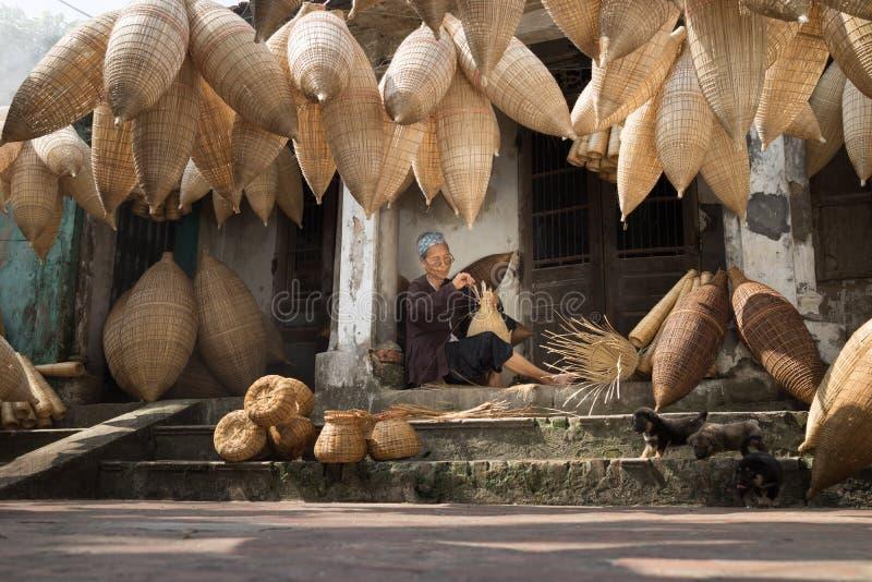 Hung Yen Vietnam - Juli 9, 2016: Den gamla husgården med många bambufiskfälla och kvinnlighantverkaren som gör traditionell bambu arkivfoton