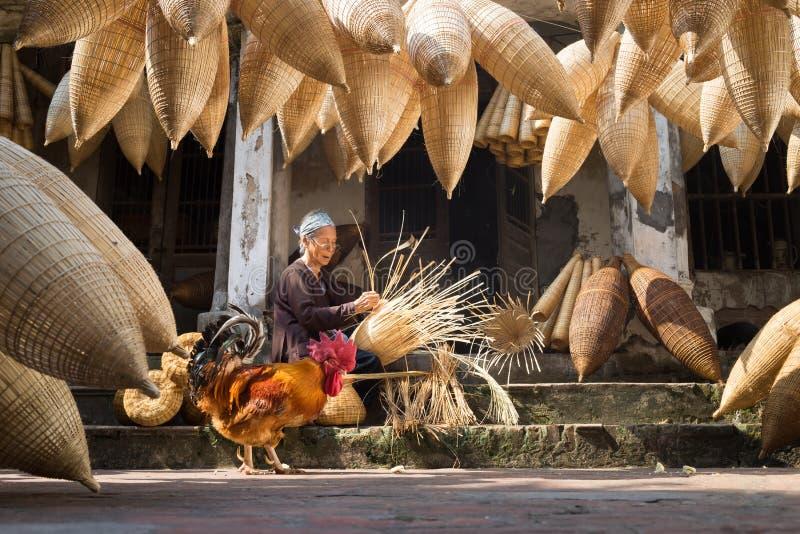 Hung Yen Vietnam - Juli 9, 2016: Gammal husgård med många bambufiskfälla, en hane och kvinnlig hantverkare som gör traditionell b arkivbild