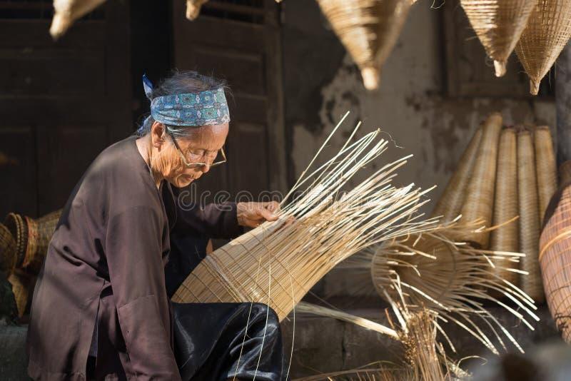 Hung Yen, Vietnam - 9. Juli 2016: Weiblicher Handwerker, der traditionelle Bambusfischfalle an ihrem alten Haus im Thu Sy-Handels stockbild