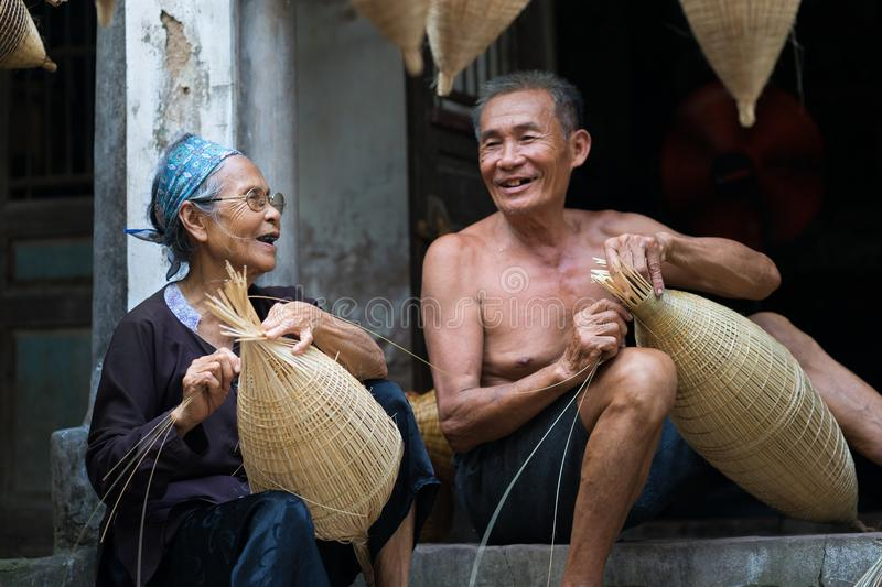 Hung Yen, Vietnam - July 9, 2016: Couple craftsmen making traditional bamboo fish trap at her old house in Thu Sy trade village.  royalty free stock image