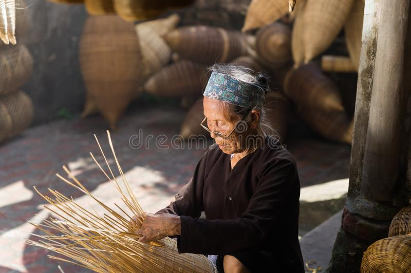 Hung Yen, Vietnam - July 9, 2016: Female craftsman making traditional bamboo fish trap at her old house in Thu Sy trade village royalty free stock image