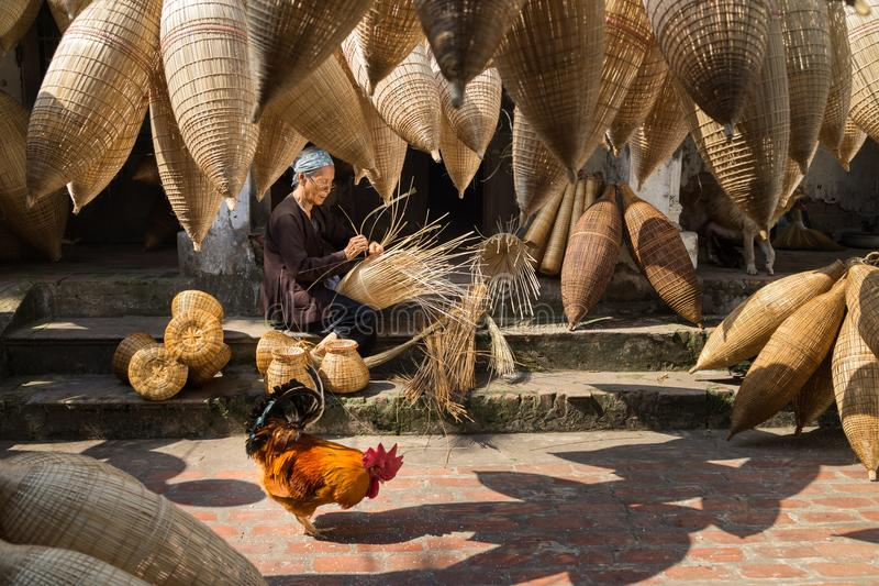 Hung Yen, Vietnam - July 9, 2016: Old house yard with many bamboo fish trap, a cock, and female craftsman making traditional bambo. O fish trap at her old house royalty free stock image