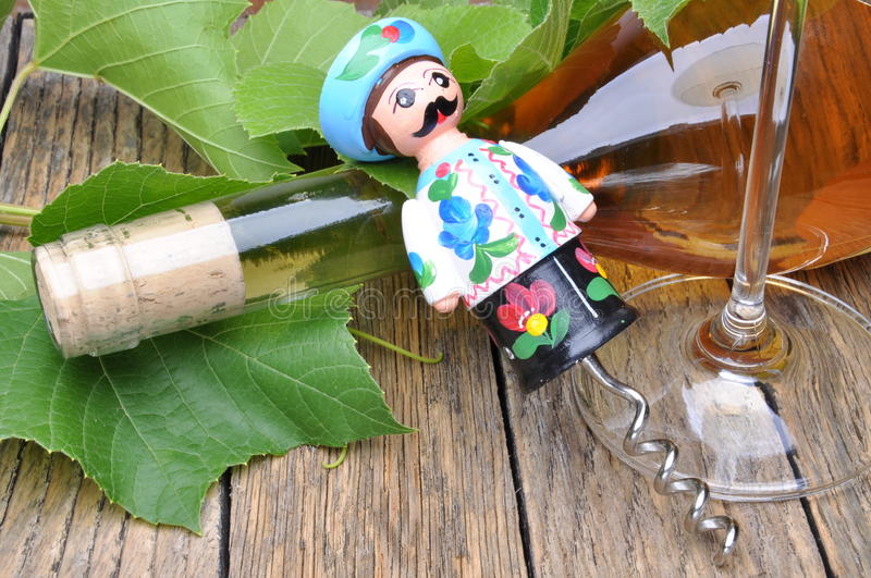 Hungarian decorative corkscrew, wine bottle and glass of wine on the wooden table. With green twigs vine royalty free stock image