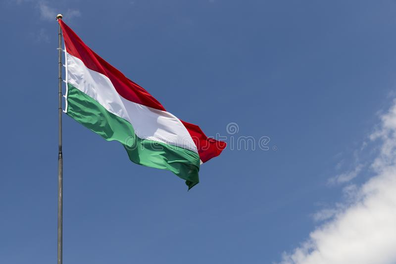 Hungarian flag on blue sky. Europe, color, patriotic, pole, symbol, wind, travel, patriotism, culture, green, national, white, red, hungary, wave, sign stock photo