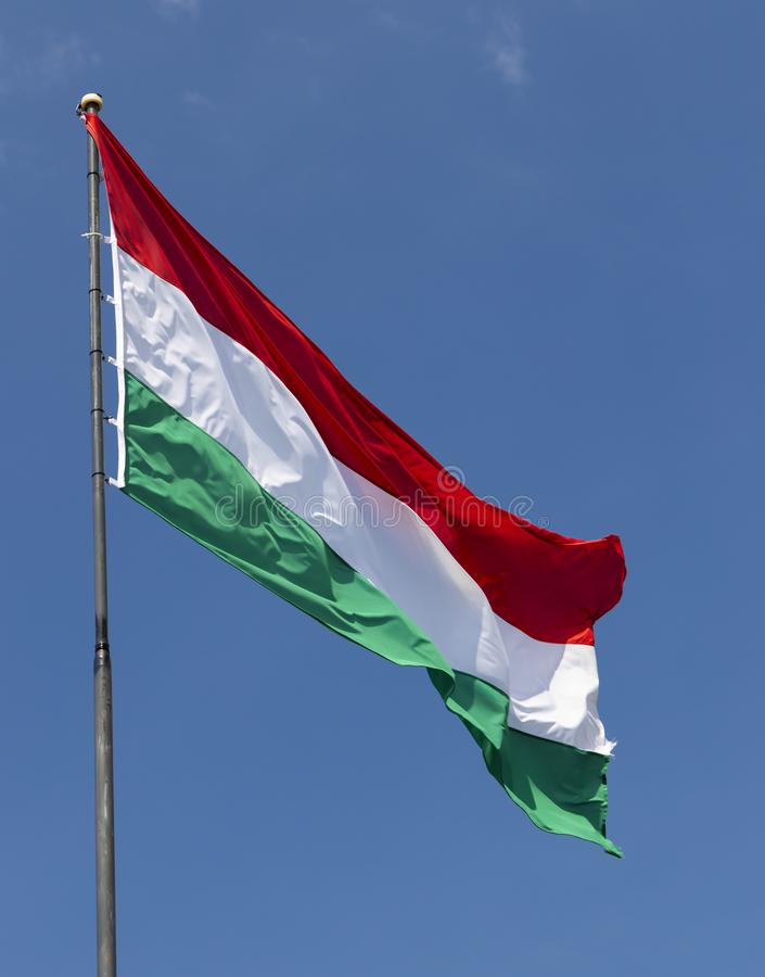 Hungarian flag on blue sky. Europe, color, patriotic, pole, symbol, wind, travel, patriotism, culture, green, national, white, red, hungary, wave, sign stock image