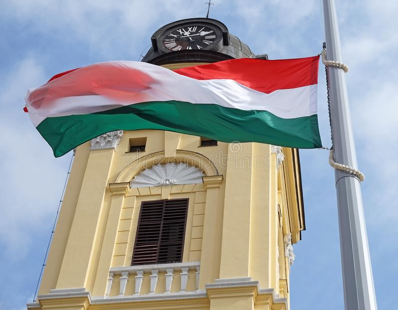 Hungarian flag on a pole next to a chuch tower. Outdoors royalty free stock image