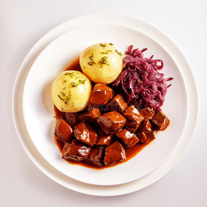 Hungarian meal of traditional savory beef stew. In thick sauce served with cabbage and potatoes stock photo