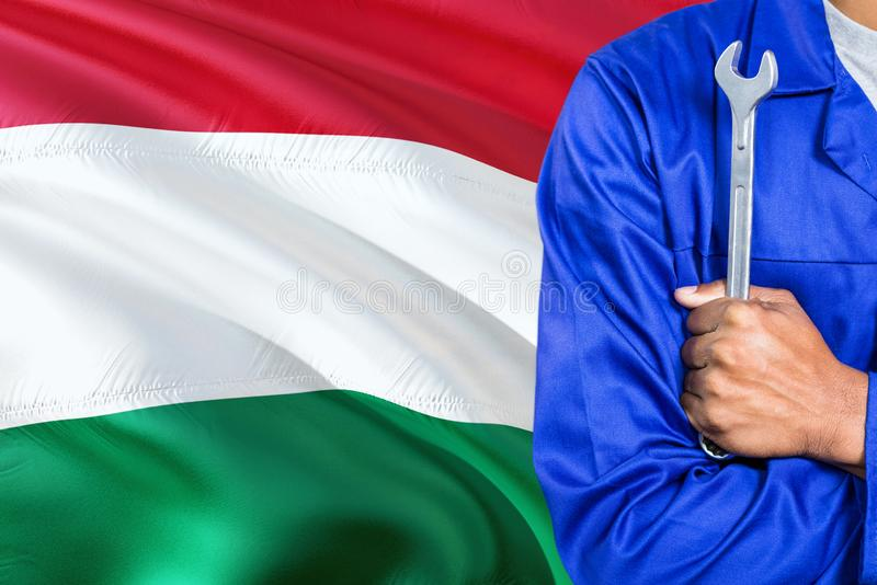 Hungarian Mechanic in blue uniform is holding wrench against waving Hungary flag background. Crossed arms technician royalty free stock photos