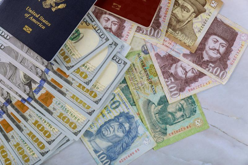 The Hungarian passports and American passport with money banknotes american hundred dollar bills and forints in dual citizenship royalty free stock photos