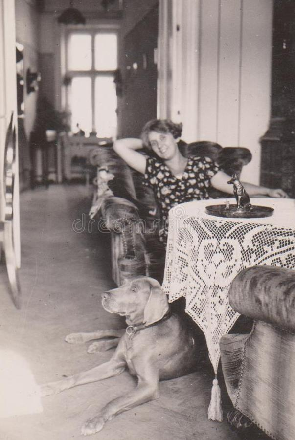 DT00076 HUNGARY CIRCA 1940 -WOMAN Sitting on a Chair in her Living Room with her Hound. HUNGARY, CIRCA 1940 -WOMAN Sitting on a Chair in her Living Room with her stock image