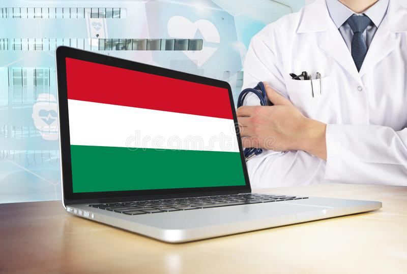 Hungary healthcare system in tech theme. Hungarian flag on computer screen. Doctor standing with stethoscope in hospital. Cryptocurrency and Blockchain concept stock photography