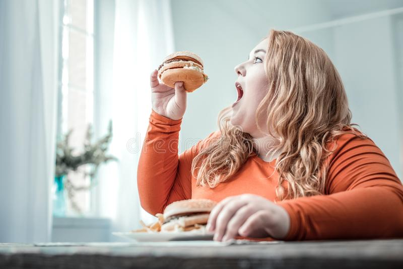 Hungrig blond fyllig kvinna som äter sjuklig mat fotografering för bildbyråer