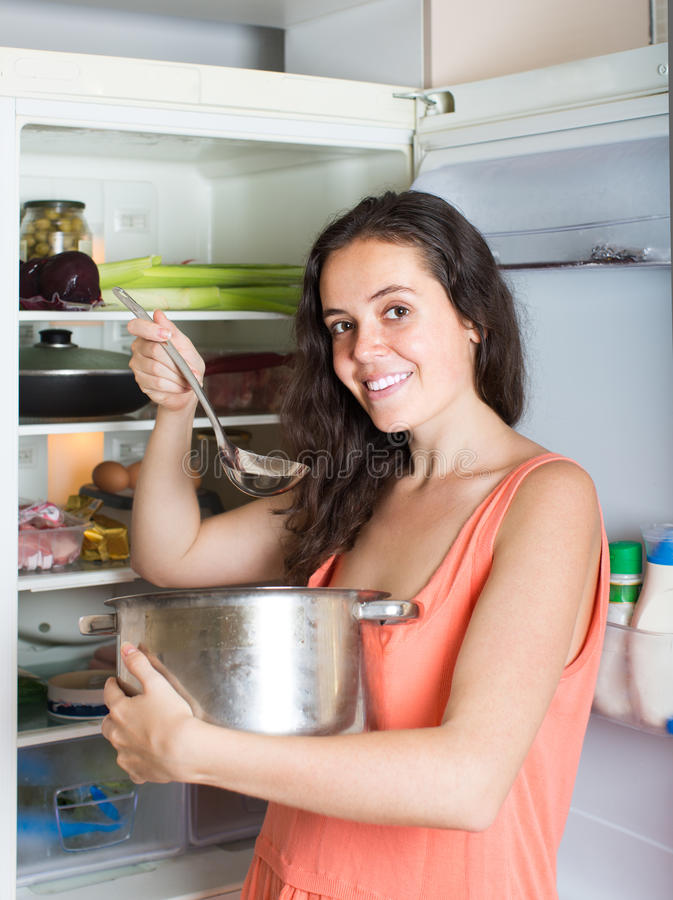 Hungrig flicka som äter från pannan arkivbilder