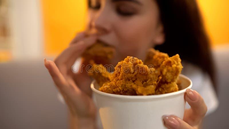 Hungrig flicka som äter stekt kycklingvingar, böjelse till sjuklig men smaklig mat royaltyfri bild