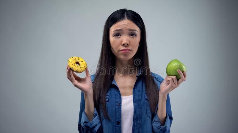 Hungrig flicka som f?rs?ker att v?lja mellan munken och ?pplet, sunt ?ta, frestelse fotografering för bildbyråer