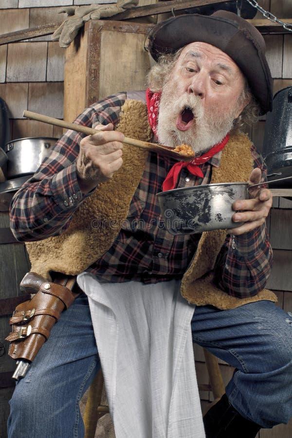 Hungrig gammal cowboy som äter bönor från en kastrull royaltyfri fotografi