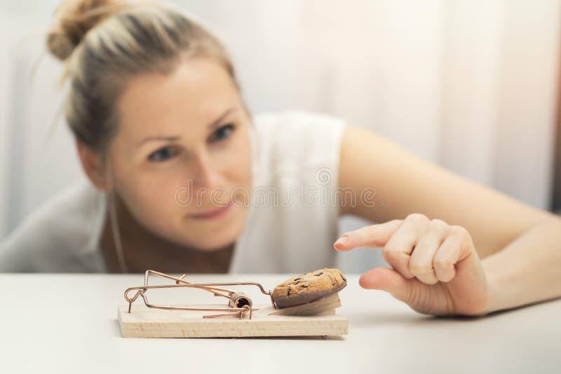 Hungrig kvinna som försöker att stjäla kakan från musfälla arkivbild