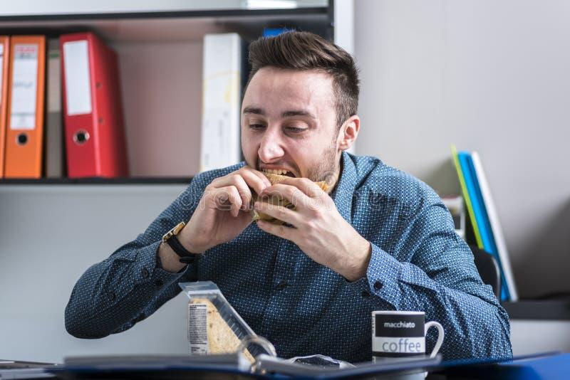 Hungrig man som äter en smörgås royaltyfri bild