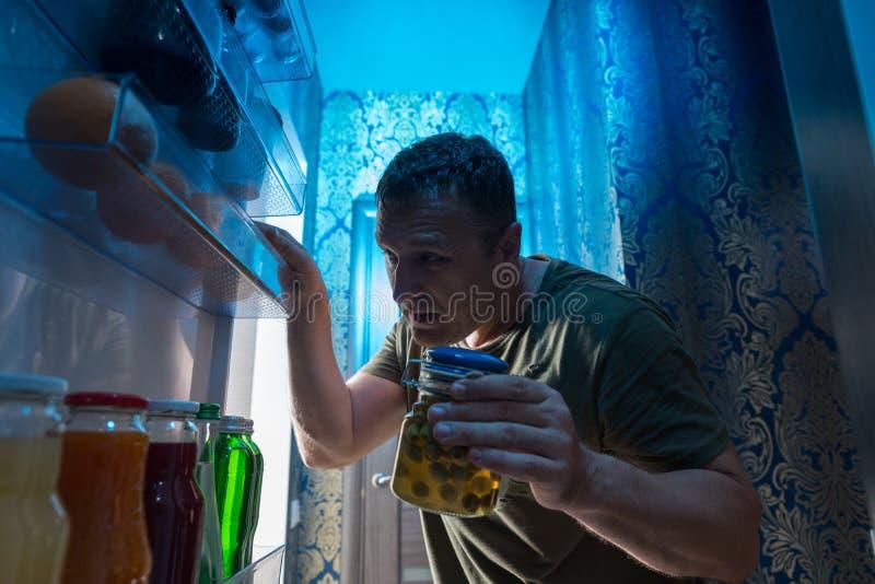 Hungrig man som plundrar hans kyl på natten royaltyfri bild